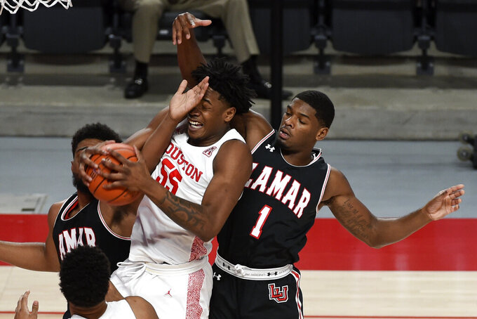 Houston forward Brison Gresham (55) grabs a rebound from Lamar guard Quinlan Bennett (1) during the first half of an NCAA college basketball game, Wednesday, Nov. 25, 2020, in Houston. (AP Photo/Eric Christian Smith)