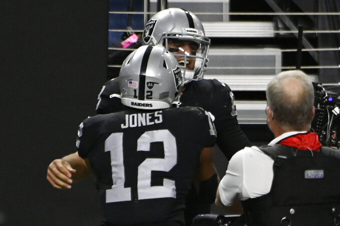 Las Vegas Raiders wide receiver Zay Jones (12) celebrates with quarterback Marcus Mariota after Mariota scored a touchdown against the Los Angeles Chargers during the second half of an NFL football game, Thursday, Dec. 17, 2020, in Las Vegas. (AP Photo/David Becker)