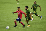 FC Dallas forward Franco Jara, left, brings the ball up the pitch on Portland Timbers midfielder Eryk Williamson, center, and Portland Timbers midfielder Diego Chara, right, during the first half of an MLS soccer match in Portland, Ore., Sunday, Nov. 22, 2020. (AP Photo/Steve Dykes)