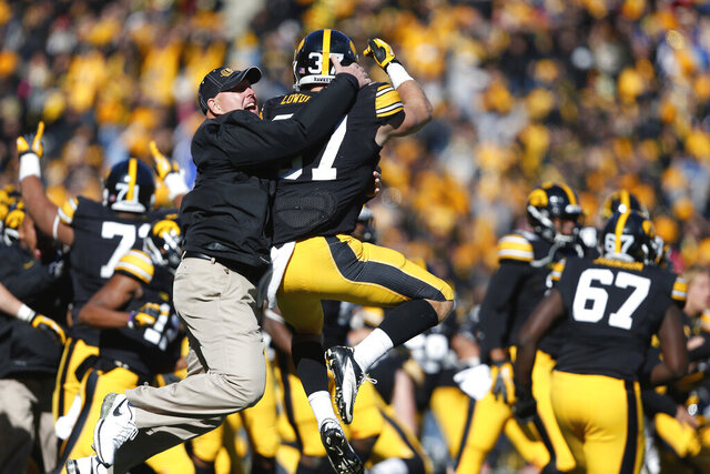 FILE - In this Oct. 26, 2013, file photo, Iowa strength and conditioning coach Chris Doyle, front left, celebrates with defensive back John Lowdermilk (37) following their win in overtime against Northwestern in an NCAA college football game  in Iowa City, Iowa. Iowa football strength and conditioning coach Doyle has been placed on administrative leave after several black former players posted on social media about what they described as systemic racism in the program. Head coach Kirk Ferentz made the announcement Saturday, June 6, 2020, calling it