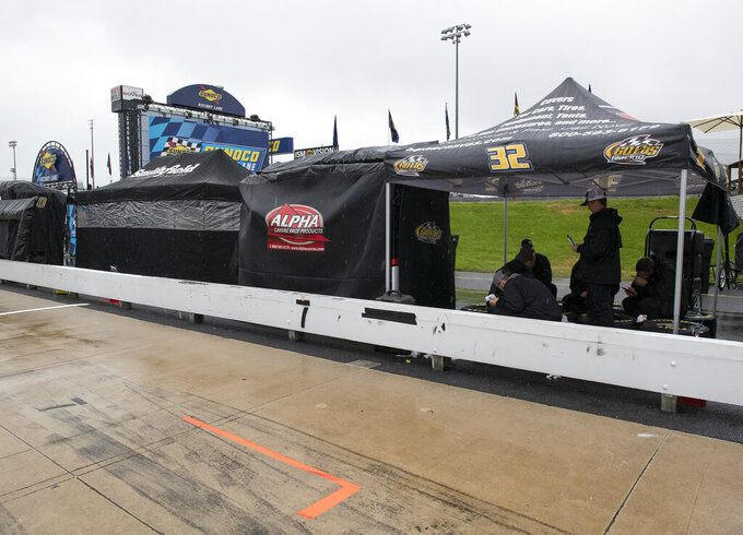 People keep dry under a tent in the pits as rain falls before the start of a NASCAR Cup series auto race at Dover International Speedway in Dover, Del., Sunday, May 5, 2019 (AP Photo/Jason Minto)