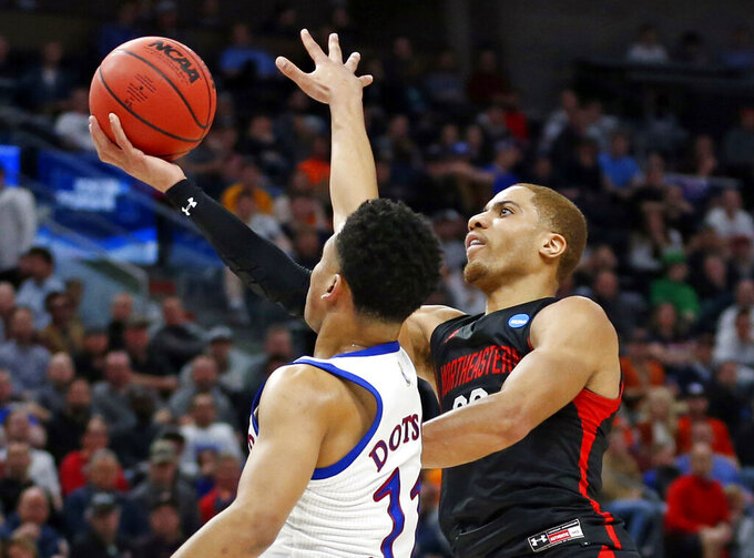 FILE - In this March 21, 2019, file photo, Northeastern guard Donnell Gresham Jr., right, lays up the ball as Kansas guard Devon Dotson (11) defends during the first half the NCAA college basketball tournament in Salt Lake City. Georgia has added Gresham, a graduate transfer from Northeastern, to its backcourt for next season, coach Tom Crean announced Thursday, May 9, 2019.  The 6-foot-2 guard started 33 games and averaged 9.7 points last season as Northeastern won 23 games and lost to Kansas in the NCAA Tournament. (AP Photo/Rick Bowmer, File)