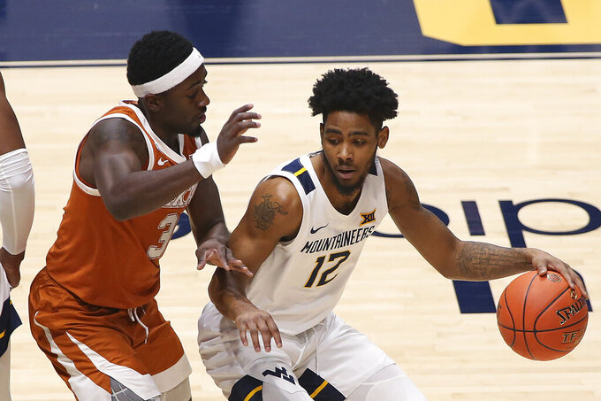 West Virginia guard Taz Sherman (12) is defended by Texas guard Courtney Ramey (3) during the first half of an NCAA college basketball game Saturday, Jan. 9, 2021, in Morgantown, W.Va. (AP Photo/Kathleen Batten)