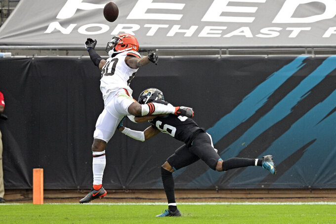 Cleveland Browns wide receiver Jarvis Landry, left, reaches but can't make a catch as Jacksonville Jaguars cornerback Luq Barcoo tries to break it up during the first half of an NFL football game, Sunday, Nov. 29, 2020, in Jacksonville, Fla. (AP Photo/Phelan M. Ebenhack)