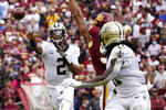 New Orleans Saints quarterback Jameis Winston (2) throws a touchdown pass to running back Alvin Kamara in the second half of an NFL football game against the Washington Football Team, Sunday, Oct. 10, 2021, in Landover, Md. (AP Photo/Alex Brandon)