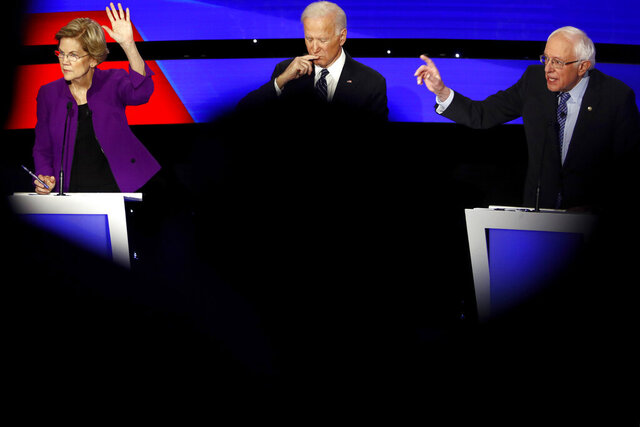 FILE - In this Jan. 14, 2020, file photo Democratic presidential candidate Sen. Elizabeth Warren, D-Mass., and Sen. Bernie Sanders, I-Vt., raise their hands to answer a question as Joe Biden pauses during a Democratic presidential primary debate hosted by CNN and the Des Moines Register in Des Moines, Iowa. Bernie Sanders is warning that if Joe Biden doesn't do more to promote his policies and reach out to Latino voters he's at risk of falling short to President Donald Trump this November. (AP Photo/Patrick Semansky, File)