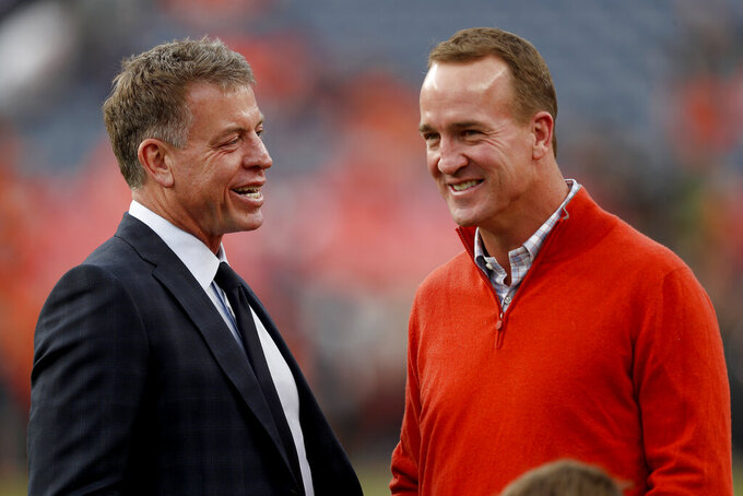 Former NFL quarterbacks Peyton Manning, right, and Troy Aikman talk prior to an NFL football game between the Kansas City Chiefs and the Denver Broncos, Thursday, Oct. 17, 2019, in Denver. (AP Photo/David Zalubowski)