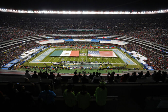 The flags of Mexico and the United States cover the field before an NFL football game between the Los Angeles Chargers and the Kansas City Chiefs Monday, Nov. 18, 2019, in Mexico City. (AP Photo/Eduardo Verdugo)