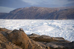 CORRECTING DATE TO 20 - In this Aug. 16, 2019, photo, New York University student researchers sit on a rock overlooking the Helheim glacier in Greenland.  U.S. President Trump announced his decision to postpone an early September visit to Denmark by tweet Tuesday Aug. 20, 2019, after Danish Prime Minister Mette Frederiksen dismissed the notion of selling Greenland to the U.S. as