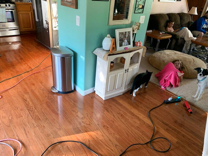 This Sunday, Oct. 6, 2019, photo provided by Kyla Awalt shows Chole Awalt, front, and her brother Colton Awalt sitting on the couch while electrical cords are seen running through the house from a generator outside during Pacific Gas and Electric's shutoff in Paradise, Calif. When the nation's largest utility warned customers that it would cut power to nearly 2 million people across Northern California, many rushed out to buy portable generators, knowing the investment could help sustain them as blackouts became a recurring fact of life. Others had the security of knowing they could rely on solar panels and batteries installed in their homes when the lights went out. (Kyla Awalt via AP)