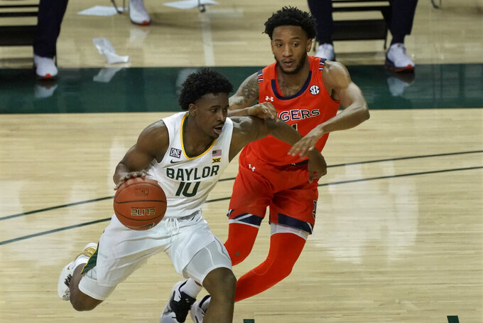 Baylor's Adam Flagler, left, drives against Auburn's Jamal Johnson, right, during the first half of an NCAA college basketball game in Waco, Texas, Saturday, Jan. 30, 2021. (AP Photo/Chuck Burton)