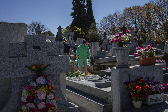 An undertaker wearing a garbage bag atop of a gown as a safety mesure during the coronavirus outbreak works at cemetery in Madrid, Spain, Thursday, March 25, 2020. The new coronavirus causes mild or moderate symptoms for most people, but for some, especially older adults and people with existing health problems, it can cause more severe illness or death. (AP Photo/Bernat Armangue)