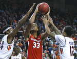 Auburn forward Anfernee McLemore (24) and Auburn guard J'Von McCormick (12) defend a shot by Georgia forward Nicolas Claxton (33) during the first half of an NCAA college basketball game Saturday, Jan. 12, 2019, in Auburn, Ala. (AP Photo/Julie Bennett)