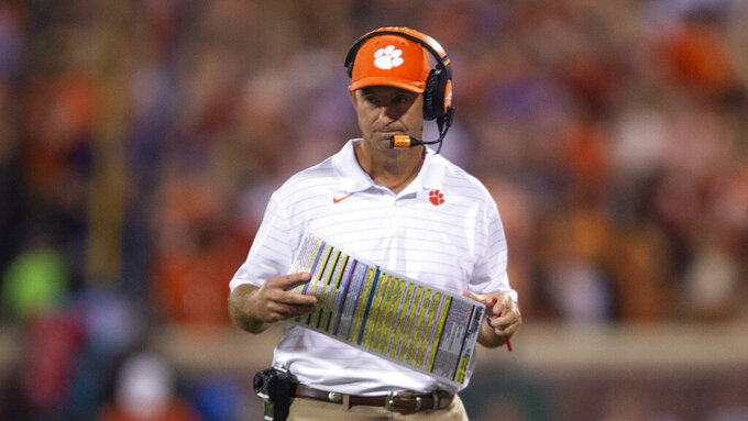 Clemson head coach Dabo Swinney looks at his play card during the first half of an NCAA college football game against Boston College Saturday, Oct. 2, 2021, in Clemson, S.C. (AP Photo/Hakim Wright Sr.)