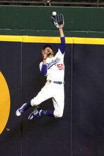 Los Angeles Dodgers right fielder Mookie Betts makes a catch and robs a home run from Atlanta Braves' Freddie Freeman during the fifth inning in Game 7 of a baseball National League Championship Series, Sunday, Oct. 18, 2020, in Arlington, Texas. (Curtis Compton/Atlanta Journal-Constitution via AP)