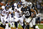 Oakland Raiders running back Josh Jacobs runs with the ball as Denver Broncos defensive end DeMarcus Walker (57) and nose tackle Mike Purcell (98) look on during the first half of an NFL football game Monday, Sept. 9, 2019, in Oakland, Calif. (AP Photo/D. Ross Cameron)