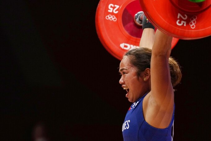 Hidilyn Diaz of Philippines celebrates as she competes and sets new world record and won the gold medal in the women's 55kg weightlifting event, at the 2020 Summer Olympics, Monday, July 26, 2021, in Tokyo, Japan. (AP Photo/Luca Bruno)