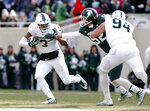 FILE - In this Saturday, April 7, 2018 file photo, Michigan State running back LJ Scott, left, rushes against defensive end Dillon Alexander as offensive lineman Chase Gianacakos (94) blocks during the first half of a spring NCAA college football scrimmage in East Lansing, Mich. The NFL can wait for now. LJ Scott is back at Michigan State with a list of areas he'd like to shore up. Scott's return after his junior season was big news for the Spartans, who now look like Big Ten title contenders in 2018. (AP Photo/Al Goldis)