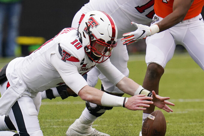 Texas Tech quarterback Alan Bowman (10) recovers his own fumble in the second half of an NCAA college football game against Oklahoma State in Stillwater, Okla., Saturday, Nov. 28, 2020. (AP Photo/Sue Ogrocki)