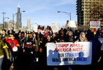 FILE - In this Friday, March 11, 2016 file photo, protestors march in Chicago before a rally for Republican presidential candidate Donald Trump at the University of Illinois-Chicago. In 2019, The Associated Press reported on a manipulated version of this photo circulating online with the foreground sign's slogan changed. An altered copy which included