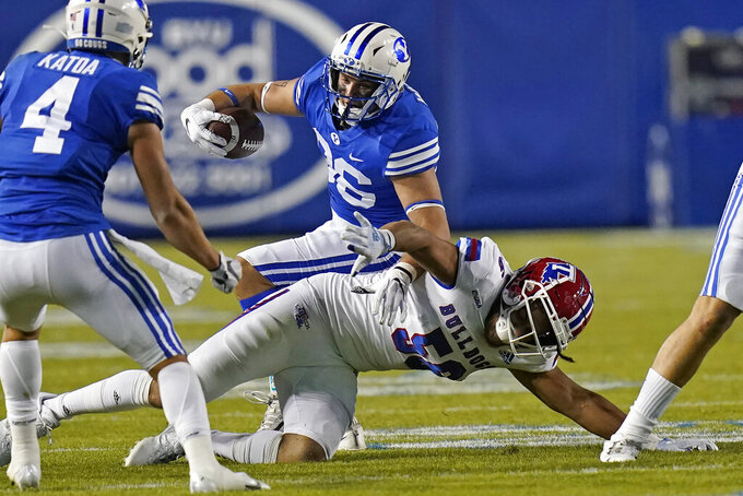 BYU tight end Carter Wheat, rear, is tackled by Louisiana Tech defensive lineman Mykol Clark (56) during the first half of an NCAA college football game Friday, Oct. 2, 2020, in Provo, Utah. (AP Photo/Rick Bowmer, Pool)