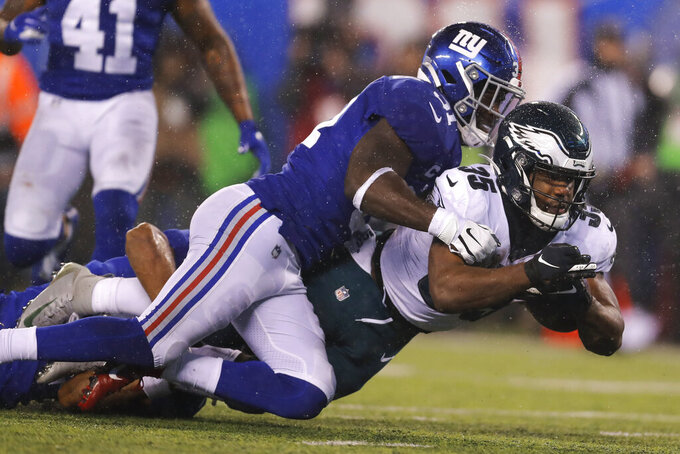 Philadelphia Eagles running back Boston Scott (35) falls with the ball in front of New York Giants defensive back Michael Thomas (31) in the second half of an NFL football game, Sunday, Dec. 29, 2019, in East Rutherford, N.J. (AP Photo/Adam Hunger)