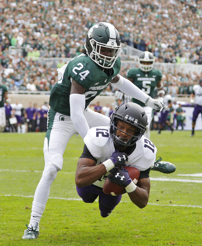 Northwestern's JJ Jefferson (12) catches a pass for a touchdown against Michigan State's Tre Person (24) during the second quarter of an NCAA college football game, Saturday, Oct. 6, 2018, in East Lansing, Mich. (AP Photo/Al Goldis)