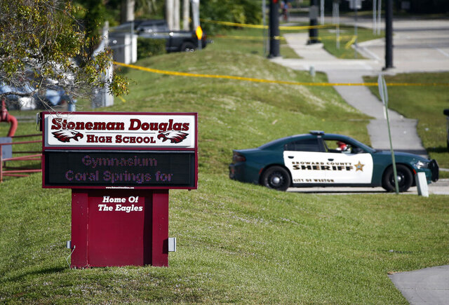 FILE- In this Feb. 15, 2018, file photo, law enforcement officers block off the entrance to Marjory Stoneman Douglas High School in Parkland, Fla., following a deadly shooting at the school. A California man who is on the autism spectrum was sentenced Monday, March 2, 2020, to more than five years in prison for cyberstalking families of Parkland, Florida, school shooting victims. (AP Photo/Wilfredo Lee, File)