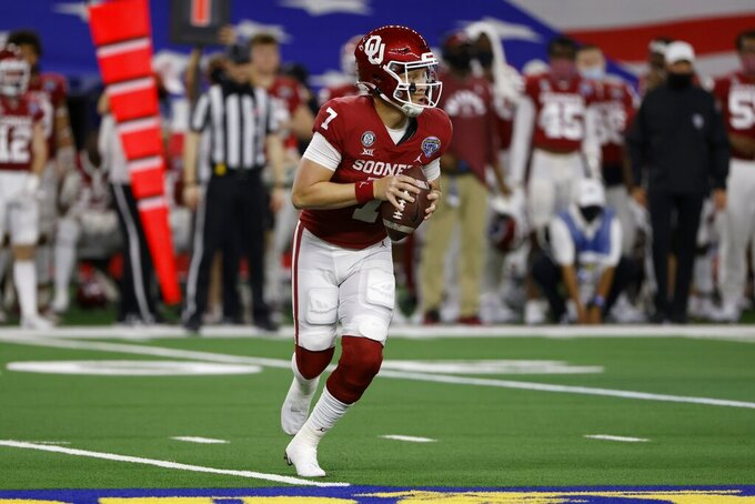 Oklahoma quarterback Spencer Rattler looks for a receiver during the first half of the team's Cotton Bowl NCAA college football game against Florida in Arlington, Texas, Wednesday, Dec. 30, 2020. (AP Photo/Ron Jenkins)