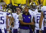 Washington coach Jimmy Lake cheers on the team's defense which held Michigan to a field goal in the first quarter of an NCAA college football game in Ann Arbor, Mich., Saturday, Sept. 11, 2021. (AP Photo/Tony Ding)