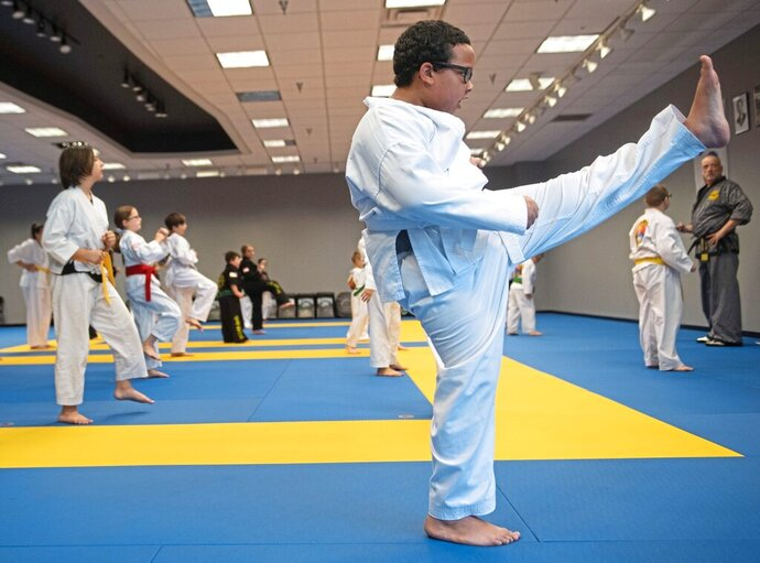 In this Tuesday, June 23, 2020 photo, Ja'kai Williams, 8, of Monaca, kicks during class at H&H Family Martial Arts Academy in the Beaver Valley Mall in Monaca, Pa. Contact sports with no contact sounds impossible, but it's become the new normal for martial arts studios throughout the pandemic. Students at H&H Family Martial Arts Academy in Monaca, Beaver County, run to a designated dot spaced six feet away from the next. There will be no interaction with friends as they would on a normal day. Instead, students are expected to keep to themselves — even the five-year-olds.(Emily Matthews/Pittsburgh Post-Gazette via AP)
