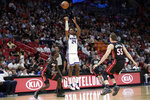 Sacramento Kings guard Buddy Hield (24) attempts a 3-pointer over Miami Heat guard Kendrick Nunn, left, and forward Duncan Robinson (55) during the first half of an NBA basketball game, Monday, Jan. 20, 2020, in Miami. (AP Photo/Lynne Sladky)