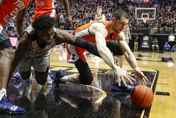 Purdue forward Trevion Williams (50) and Illinois forward Giorgi Bezhanishvili (15) go for a loose ball during the second half of an NCAA college basketball game in West Lafayette, Ind., Tuesday, Jan. 21, 2020. Illinois defeated Purdue 79-62. (AP Photo/Michael Conroy)