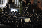 Orthodox Jewish men carry Moshe Deutsch's casket outside a Brooklyn synagogue following his funeral, Wednesday, Dec. 11, 2019 in New York. Deutsch was killed Tuesday in a shooting inside a Jersey City, N.J. kosher food market. (AP Photo/Mark Lennihan)