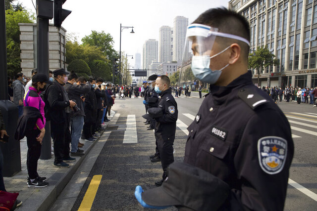 People and policemen bow their heads during a national moment of mourning for victims of coronavirus in Wuhan in central China's Hubei Province, Saturday, April 4, 2020. With air raid sirens wailing and flags at half-staff, China on Saturday held a three-minute nationwide moment of reflection to honor those who have died in the coronavirus outbreak, especially
