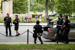 Lewis Sanchez, center, sits after being handcuffed by Secret Service agents along Constitution Avenue near the White House in the morning as protests continue over the death of George Floyd in Washington, Tuesday, June 2, 2020. Floyd died after being restrained by Minneapolis police officers. Sanchez and three other friends were stopped as they returned to their car after spending the night at a strangers home because of a District of Columbia city wide curfew. Agents later released Sanchez. (AP Photo/Andrew Harnik)
