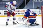 New York Islanders goaltender Semyon Varlamov (40) deflects a shot on goal by New York Rangers' Alexis Lafrenière (13) during the first period of an NHL hockey game Saturday, May 1, 2021, in Uniondale, N.Y. (AP Photo/Frank Franklin II)