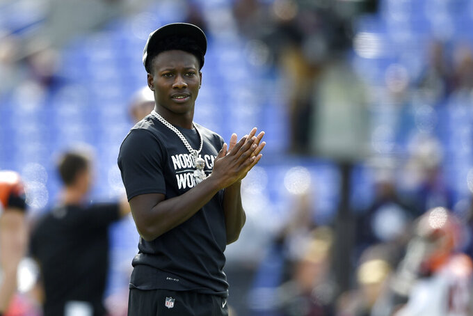 Baltimore Ravens wide receiver Marquise Brown looks on as his team works out prior to an NFL football game against the Cincinnati Bengals Sunday, Oct. 13, 2019, in Baltimore. Brown is inactive for the contest. (AP Photo/Gail Burton)