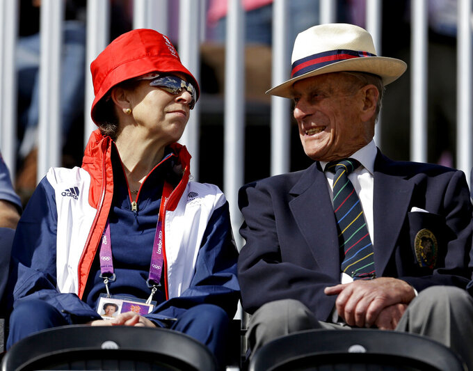 """FILE - In this Sunday, July 29, 2012 file photo, Princess Anne, left, attends the equestrian eventing dressage phase with her father Prince Phillip the Duke of Edinburgh, husband of Britain's Queen Elizabeth II, at the 2012 Summer Olympics, in London. In a message released by Buckingham Palace on Sunday, April 11, 2021, Anne praised Philip's """"ability to treat every person as an individual in their own right with their own skills,"""" a nod to the many charities and other organizations he was involved with. Prince Philip died on Friday, April 9, 2021. He was 99. (AP Photo/David Goldman, FIle)"""