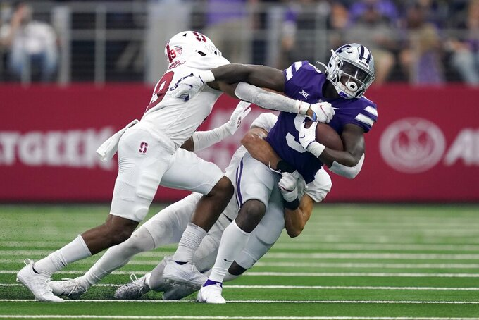 Stanford safety Noah Williams, left, and linebacker Tristan Sinclair, rear, combine to stop Kansas State running back Jacardia Wright (9) after a short gain in the second half of an NCAA college football game in Arlington, Texas, Saturday, Sept. 4, 2021. (AP Photo/Tony Gutierrez)