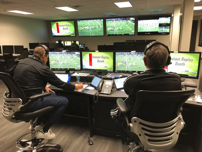Greg Burks, left, the Big 12 coordinator of football officials, and David Warden, the Big 12's replay coordinator, sit in the conference's centralized replay center in Irving, Texas, Thursday, Oct. 25, 2018. In the background at rear left, at one of the centers six game stations, is the two-man crew assigned specifically to cover the Baylor-West Virginia NCAA college football game. (AP Photo/Stephen Hawkins)