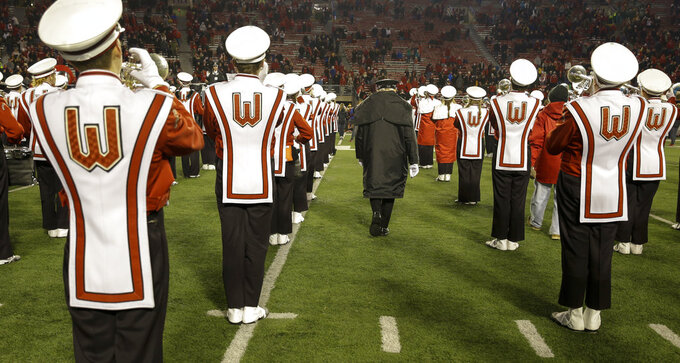 University of Wisconsin-Madison Marching Band Director Mike Leckrone walks between playing band members after an NCAA college football game Saturday, Nov. 24, 2018, in Madison, Wis. Leckrone is retiring after 50 years of directing the UW band. Minnesota beat Wisconsin 37-15. (AP Photo/Andy Manis)