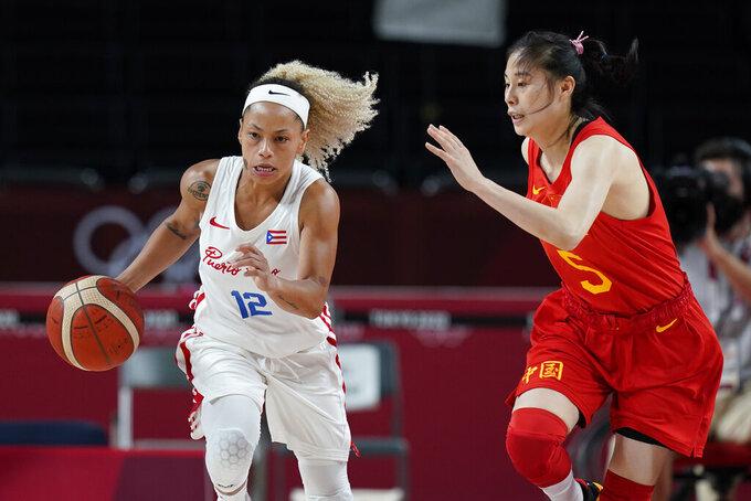 Puerto Rico's Dayshalee Salaman (12) drives on China's Siyu Wang (5) during a women's basketball preliminary round game at the 2020 Summer Olympics in Saitama, Japan, Tuesday, July 27, 2021. (AP Photo/Eric Gay)