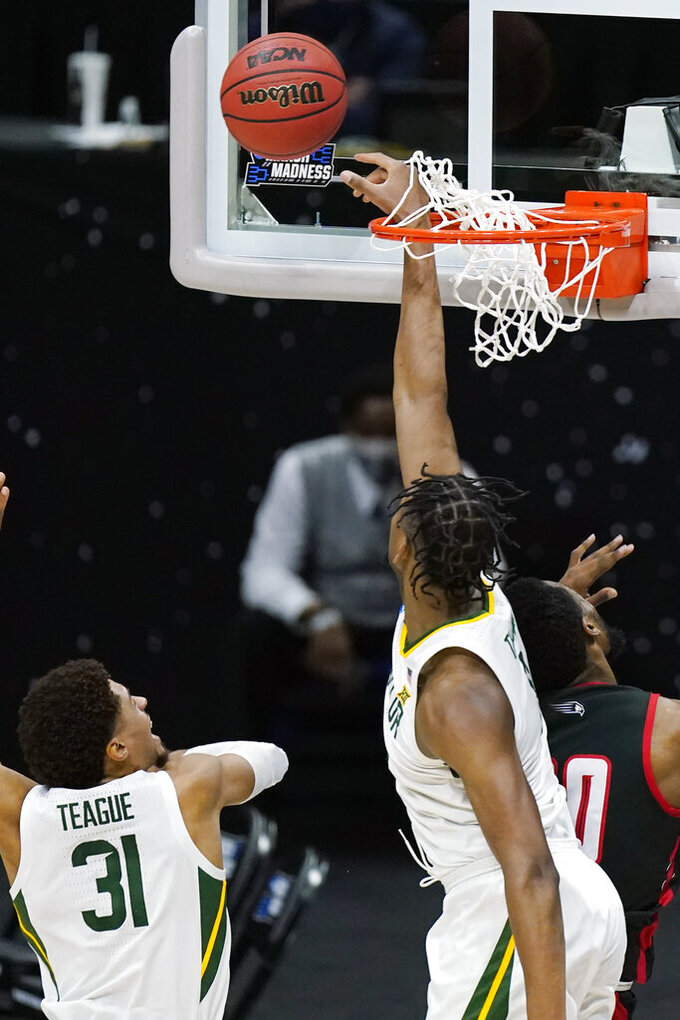 Baylor's Flo Thamba, right, reaches through the net to block a shot against Hartford during the second half of a college basketball game in the first round of the NCAA tournament at Lucas Oil Stadium in Indianapolis Friday, March 19, 2021, in Indianapolis, Tenn. (AP Photo/Mark Humphrey)