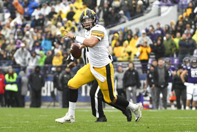 Iowa quarterback Nate Stanley (4) looks to pass against Northwestern during the second half of an NCAA college football game, Saturday, Oct. 26, 2019, in Evanston, Ill. (AP Photo/David Banks)