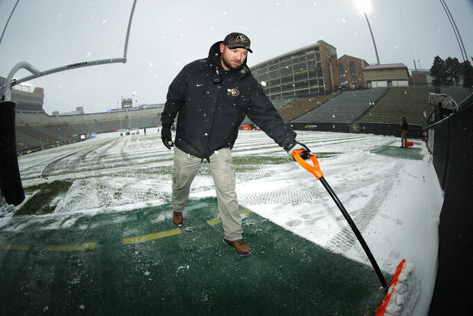 Ryan Newman, director of athletic grounds for the University of Colorado, clears snow from the playing surface in Folsom Field before the first half of an NCAA college football game between Utah and Colorado Saturday, Nov. 17, 2018, in Boulder, Colo. A fall storm packing light snow has swept over the interior West. (AP Photo/David Zalubowski)