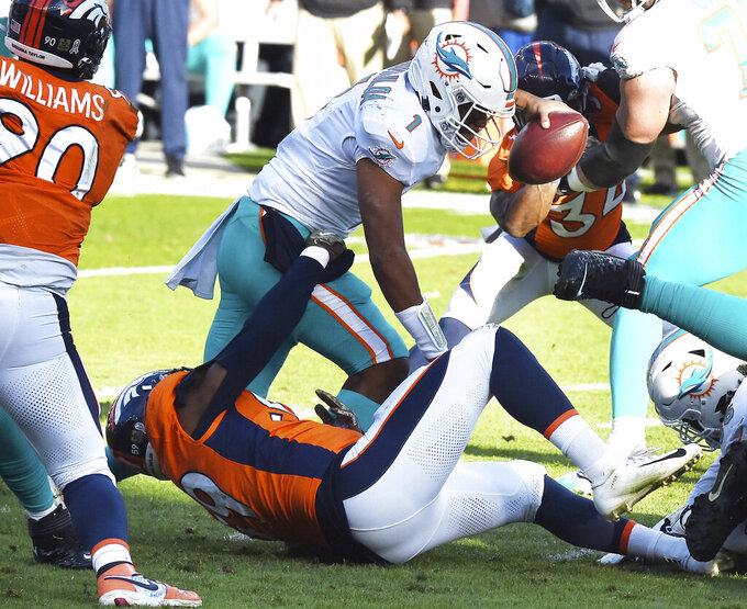 Denver Broncos linebacker Malik Reed, bottom, sacks Miami Dolphins quarterback Tua Tagovailoa, top, in the first half of an NFL football game in Denver, Sunday, Nov. 22, 2020. (Jerilee Bennett/The Gazette via AP)