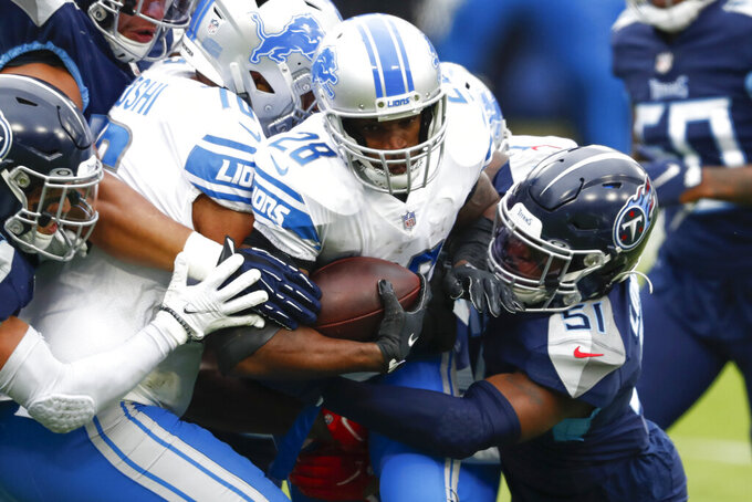 Detroit Lions running back Adrian Peterson is tackled by Tennessee Titans linebacker David Long during the first half of an NFL football game Sunday, Dec. 20, 2020, in Nashville, Tenn. (AP Photo/Wade Payne)