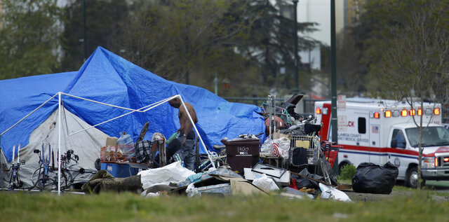 FILE - In this March 19, 2020 file photo, an ambulance drives by a homeless encampment in Oakland, Calif. City officials in Oakland, growing weary of a ballooning homeless population, approved a contentious new policy that will prohibit homeless people from setting up tents in parks or near homes, businesses, schools and some churches. (AP Photo/Ben Margot,File)