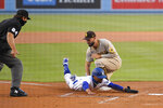 Los Angeles Dodgers' Mookie Betts, right, is tagged out by San Diego Padres' Eric Hosmer after getting caught in a rundown as home plate umpire John Libka watches during the first inning of a baseball game Monday, Aug. 10, 2020, in Los Angeles. (AP Photo/Mark J. Terrill)